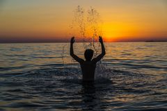 Muchacho del adolescente que se baña en el mar en la puesta del sol en Sicilia Fotografía de archivo