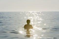 Muchacho del adolescente que se baña en el mar rodeado por la reflexión del rayo de sol Fotografía de archivo