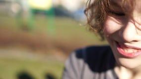 Muchacho del adolescente que se divierte con el carrusel en patio al aire libre Ocio activo del deporte de la primavera o del oto metrajes
