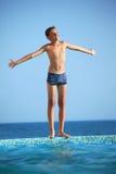 Muchacho del adolescente que se opone la piscina cercana al mar Fotos de archivo libres de regalías