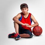 Muchacho del adolescente que se sienta con baloncesto Fotos de archivo libres de regalías