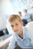 Muchacho del adolescente que se sienta en el sofá Foto de archivo