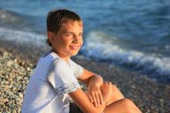 Muchacho del adolescente que se sienta en la costa de piedra Imagen de archivo