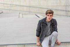 Muchacho del adolescente que se sienta en las escaleras felices Fotos de archivo libres de regalías
