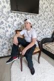 Muchacho del adolescente que se sienta en una silla en sala de estar Fotografía de archivo