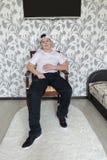 Muchacho del adolescente que se sienta en una silla en sala de estar Imagen de archivo libre de regalías