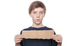 Muchacho del adolescente que sostiene un pedazo marrón de cartulina adentro Fotografía de archivo