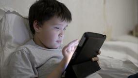 Muchacho del adolescente que usa la tableta que miente en cama almacen de metraje de vídeo