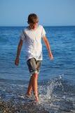 Muchacho del adolescente que va en la costa Imágenes de archivo libres de regalías