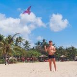 Muchacho del adolescente que vuela una cometa en la playa tropical Fotos de archivo libres de regalías