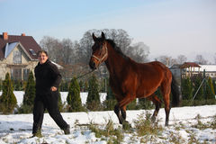 Muchacho del adolescente y caballo de bahía que corre abajo de la calle del pueblo Imagen de archivo libre de regalías
