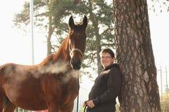 Muchacho del adolescente y caballo marrón que se colocan cerca del árbol Imagen de archivo libre de regalías
