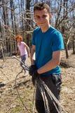 Muchacho del adolescente y su madre spring cleaning la huerta Foto de archivo libre de regalías