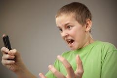Muchacho del adolescente y teléfono móvil Imagen de archivo libre de regalías