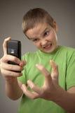 Muchacho del adolescente y teléfono móvil Imagenes de archivo