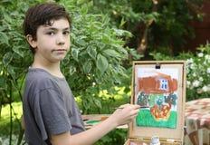 Muchacho del artista del adolescente en la imagen de la pintura del jardín de las flores del jazmín y de la casa de la cabaña Imagen de archivo libre de regalías