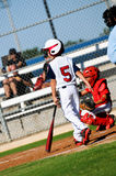Muchacho del béisbol de la juventud alrededor al palo que mira la jarra Foto de archivo libre de regalías