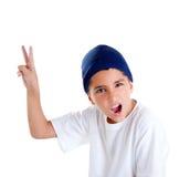 Muchacho del cabrito del casquillo azul con gesto de mano de la victoria Foto de archivo libre de regalías