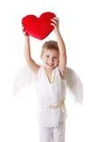 Muchacho del cupido con las alas que muestran el corazón rojo de la almohada Foto de archivo