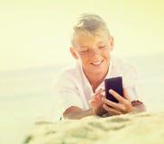 """muchacho del ¿del ï"""" que miente en la playa con el teléfono Fotografía de archivo"""