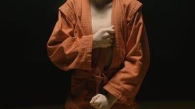 Muchacho del deportista en un kimono rojo para el judo El muchacho pone un kimono rojo con objeto del entrenamiento o del entrena Foto de archivo libre de regalías