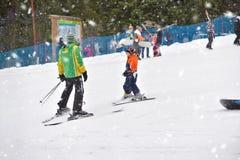 Muchacho del esquí que aprende de profesor del esquí, en traje de esquí y casco encendido Imágenes de archivo libres de regalías