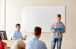 Muchacho del estudiante con el cuaderno y el profesor en la escuela Imágenes de archivo libres de regalías