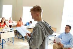 Muchacho del estudiante con el cuaderno y el profesor en la escuela Fotografía de archivo