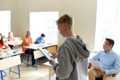 Muchacho del estudiante con el cuaderno y el profesor en la escuela Foto de archivo