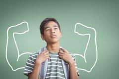 Muchacho del estudiante con el gráfico de los puños que mira para arriba contra fondo verde Fotos de archivo libres de regalías