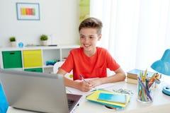 Muchacho del estudiante con el ordenador portátil que escribe al cuaderno Fotos de archivo libres de regalías