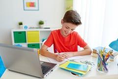 Muchacho del estudiante con el ordenador portátil que escribe al cuaderno Imagenes de archivo