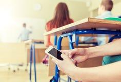 Muchacho del estudiante con el smartphone que manda un SMS en la escuela Fotos de archivo