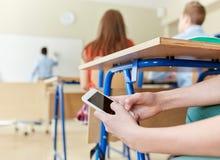 Muchacho del estudiante con el smartphone que manda un SMS en la escuela Fotos de archivo libres de regalías