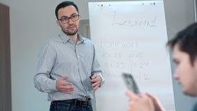 Muchacho del estudiante con el smartphone que manda un SMS en la lección de la escuela Foto de archivo libre de regalías