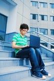 Muchacho del estudiante con la computadora portátil Foto de archivo libre de regalías