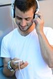 Muchacho del estudiante con los auriculares que miran abajo Fotografía de archivo