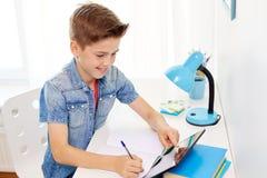 Muchacho del estudiante con PC de la tableta que escribe al cuaderno Imágenes de archivo libres de regalías