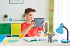 Muchacho del estudiante con PC y el cuaderno de la tableta en casa Imagen de archivo libre de regalías