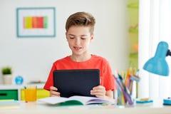 Muchacho del estudiante con PC y el cuaderno de la tableta en casa Fotografía de archivo