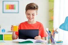 Muchacho del estudiante con PC y el jugo de la tableta en casa Imagenes de archivo