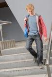 Muchacho del estudiante que camina abajo de las escaleras de la universidad Fotos de archivo libres de regalías