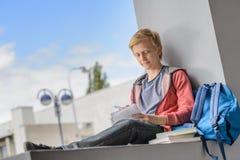 Muchacho del estudiante que estudia en el campus universitario Imagen de archivo libre de regalías