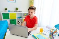 Muchacho del estudiante que mecanografía en el ordenador portátil en casa Imagenes de archivo