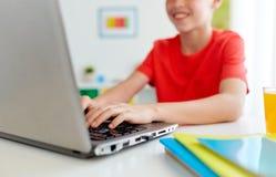 Muchacho del estudiante que mecanografía en el ordenador portátil en casa Imagen de archivo