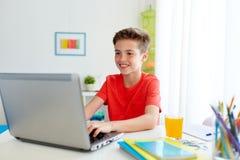 Muchacho del estudiante que mecanografía en el ordenador portátil en casa Fotografía de archivo libre de regalías