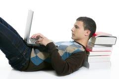 Muchacho del estudiante que miente en suelo, los libros y el ordenador Imagenes de archivo