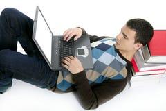 Muchacho del estudiante que miente en suelo, los libros y el ordenador Foto de archivo libre de regalías