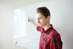 Muchacho del estudiante que muestra algo en el tablero blanco en blanco Foto de archivo libre de regalías