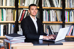 Muchacho del estudiante que trabaja en un ordenador portátil en la biblioteca Imagen de archivo